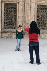 Seorang kawan sedang memotret istrinya di depan jendela mesjid