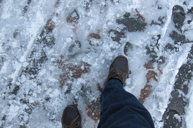 Salju yang sudah mengeras menjadi es di trotoar jalan