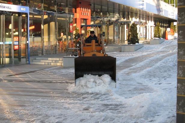 Petugas sedang membersihkan salju di area jalan kaki...